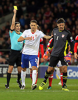 Vladimir Stojkovic of Serbia (R) sees a yellow card by match referee Alberto Mallenco (L) during the 2018 FIFA World Cup Qualifier between Wales and Serbia at the Cardiff City Stadium, Wales, UK. Saturday 12 November 2016