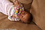 Baby girl lying on back holding and mouthing toy held with both hands