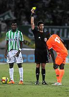 MEDELLIN - COLOMBIA -04-05-2014: Hernando Buitrago (Izq.) arbitro, muestra tarjeta amarilla a Yilmar Angulo (Der.), jugador de Envigado FC, durante partido de vuelta entre Atletico Nacional y el Envigado FC por los cuartos de final de la Liga Postobon I 2014, jugado en el estadio Atanasio Girardot de la ciudad de Medellin./ Hernando Buitrago (L), referee, shows yellow card to Yilmar Angulo (R), player of Envigado FC during a match for the second leg between Atletico Nacional and Envigado FC for the quarter of finals the Liga Postobon I 2014 at the Atanasio Girardot stadium in Medellin city. Photo: VizzorImage. / Luis Rios / Str.