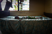 A child on a bed in a fisherman's home in central Funafuti, Tuvalu. Located in the South West Pacific Ocean, Tuvalu is the world's 4th smallest country and is one of the most vulnerable to climate change impacts including sea level rise, drought and extreme weather events. Tuvalu - March, 2019.