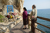 An elderly couple pay respects at a seaside shrine in Malaga, Spain.