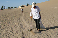 A man picks up dried up camel dung in a tourist spot in Dunhuang, Gansu Province. China