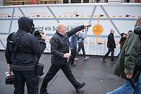 """Bis zu 2500 Anhaenger der Rechtspartei """"Alternative fuer Deutschland"""" (AfD) versammelten sich am Samstag den 7. November 2015 in Berlin zu einer Demonstration. Sie protestierten gegen die Fluechtlingspolitik der Bundesregierung und forderten """"Merkel muss weg"""". Die Demonstration sollte der Abschluss einer sog. """"Herbstoffensive"""" sein, zu der urspruenglich 10.000 Teilnehmer angekuendigt waren.<br /> Mehrere tausend Menschen protestierten gegen den Aufmarsch der Rechten und versuchten an verschiedenen Stellen die Route zu blockieren. Gruppen von AfD-Anhaengern wurden von der Polizei durch Einsatz von Pfefferspray, Schlaege und Tritte durch Gegendemonstranten, die sich an zugewiesenen Plaetzen aufhielten, zur rechten Demonstration gebracht. Zum Teil wurden sie von Neonazis-Hooligans dabei angefeuert. Dabei kam es zu Verletzten, mehrere Gegendemonstranten wurden festgenommen.<br /> Im Bild: Ein AfD-Anhaenger verfolgt missliebige Journalisten.<br /> 7.11.2015, Berlin<br /> Copyright: Christian-Ditsch.de<br /> [Inhaltsveraendernde Manipulation des Fotos nur nach ausdruecklicher Genehmigung des Fotografen. Vereinbarungen ueber Abtretung von Persoenlichkeitsrechten/Model Release der abgebildeten Person/Personen liegen nicht vor. NO MODEL RELEASE! Nur fuer Redaktionelle Zwecke. Don't publish without copyright Christian-Ditsch.de, Veroeffentlichung nur mit Fotografennennung, sowie gegen Honorar, MwSt. und Beleg. Konto: I N G - D i B a, IBAN DE58500105175400192269, BIC INGDDEFFXXX, Kontakt: post@christian-ditsch.de<br /> Bei der Bearbeitung der Dateiinformationen darf die Urheberkennzeichnung in den EXIF- und  IPTC-Daten nicht entfernt werden, diese sind in digitalen Medien nach §95c UrhG rechtlich geschuetzt. Der Urhebervermerk wird gemaess §13 UrhG verlangt.]"""