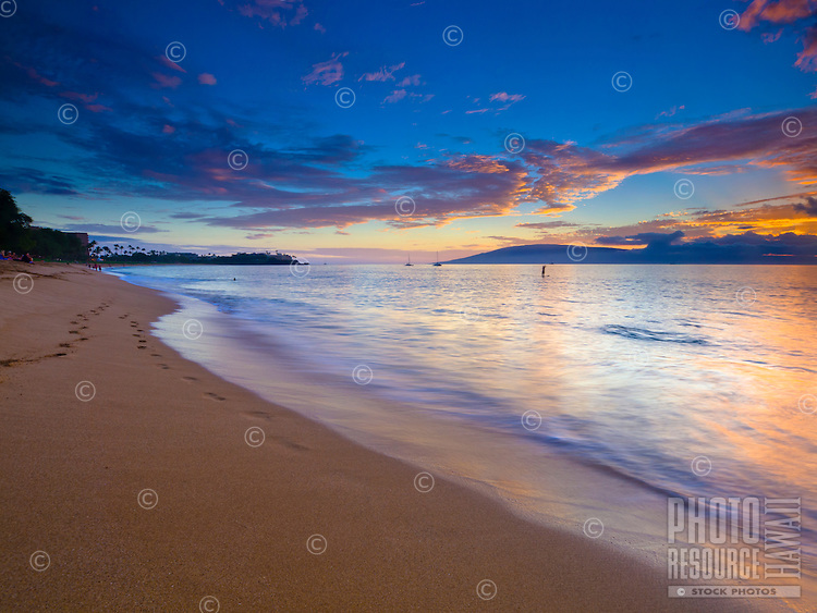 At sunset, waves slowly wash away footprints in the sand along the Ka'anapali Beach shoreline, Maui.