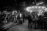 NEW YORK, NY — SEPTEMBER 24, 2020:  Demonstrators protesting against a Kentucky Grand Jury decision to not directly indict the officers involved in the shooting of Breonna Taylor, a 26 year-old EMT who was killed in her Louisville home by police on March 13th of this year, pass people dining on the sidewalk on September 24, 2020 in New York City.  Former police detective Brett Hankison faces three felony charges of wanton endangerment.  Photograph by Michael Nagle