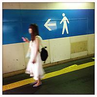 A woman walks through the Tokyo subway system.