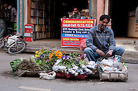 Kathmandu, Nepal.  Nepali Man Selling Flowers.  Telephone Store Behind.