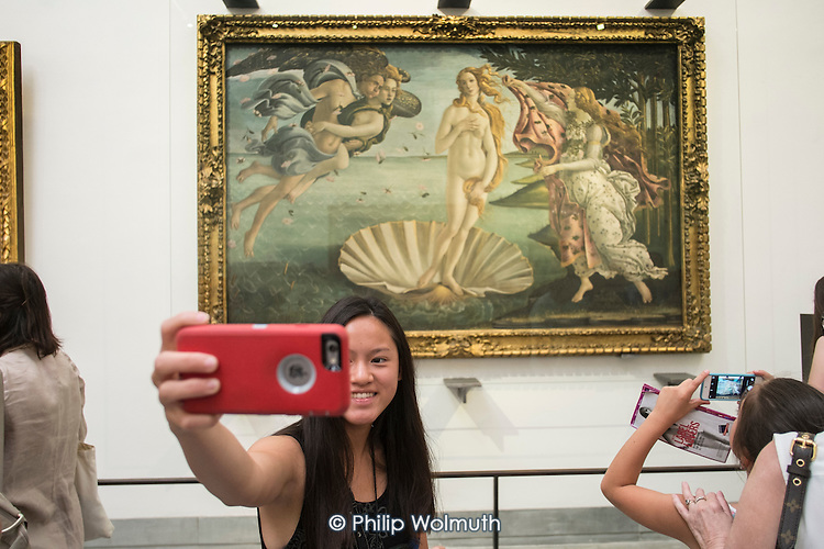 A young woman takes a selfie in front of Botticelli's Birth of Venus in the Uffizi gallery, Florence, Italy.