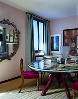 The dining room is furnished with a painted circular table and chairs upholstered in a fucshia-pink velvet