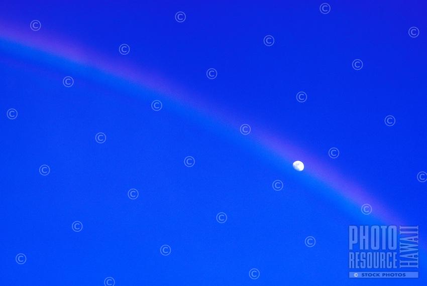 Moon peeking out of a rainbow