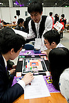 """Visitors play a card game during the Niconico Douga fan event at Makuhari Messe International Exhibition Hall on April 25, 2015, Chiba, Japan. The event includes special attractions such as J-pop concerts, Sumo and Pro Wrestling matches, cosplay and manga and various robot performances and is broadcast live on via the video-sharing site. Niconico Douga (in English """"Smiley, Smiley Video"""") is one of Japan's biggest video community sites where users can upload, view, share videos and write comments directly in real time, creating a sense of a shared watching. According to the organizers more than 200,000 viewers for two days will see the event by internet. The popular event is held in all 11 halls of the huge Makuhari Messe exhibition center from April 25 to 26. (Photo by Rodrigo Reyes Marin/AFLO)"""