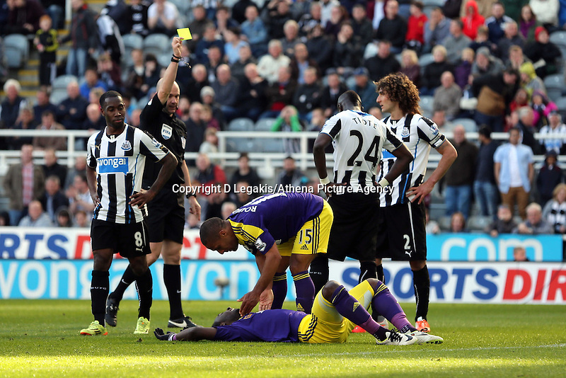 Pictured: Marvin Emnes of Swansea on the ground after he was brought down in the box in stoppage time, match referee shows a yellow card to the player who fouled him. Saturday 19 April 2014<br /> Re: Barclay's Premier League, Newcastle United v Swansea City FC at St James Park, Newcastle, UK.
