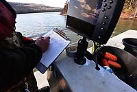 Jon Stein jots down data as fish are measured and weighed.<br />(NWA Democat-Gazette/Flip Putthoff)