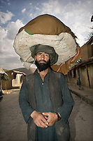 A naan seller carries his bread, wrapped to stay fresh, on his head.