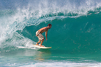 Male surfer catching a wave at Rock Piles sandbar. About to get barrelled. North shore Oahu.
