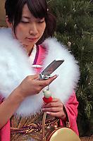 A shopper uses a mobile phone, Tokyo, Japan..