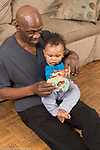 9 month old baby boy sitting on father's lap playing with new toy shown how it works by father