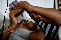 """Karla Gonzalez acompañada de su hijo Lester y pareja Melvin Ceballos intentan comunicarse con sus familiares via WhatsApp en Honduras, mientras descansan en el Comedor Comunitario de la colonia San Luis de Hermosillo Sonora. <br /> <br />  Caravana del Migrante integrada por 600 personas en su mayoría de origen centroamericano, arribo a Hermosillo a bordo del tren conocido como """"La Bestia"""", provienen de la frontera Sur del País y con rumbo a la ciudad de Mexicali donde continuaran el viaje hasta Tijuana.<br /> La caravana tiene como objetivo solicitar <br /> asilo a Estados Unidos y algunos integrantes piensan solicitar una visa humanitaria en Mexico para laborar en los campos de Sonora y Baja California.<br /> (Photo: NortePhoto/Luis Gutierrez)"""