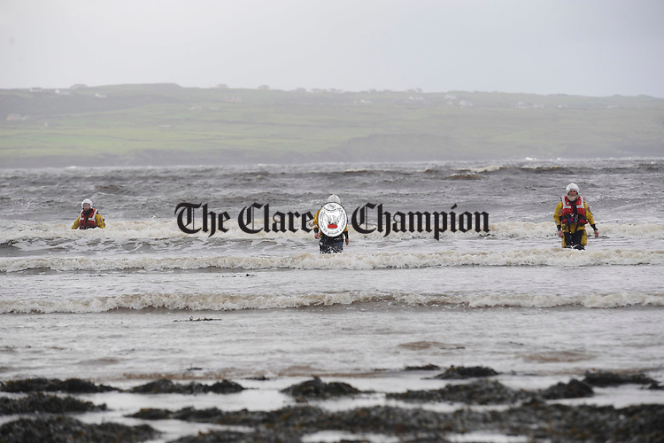 Members of the Doolin coastguard come ashore after being dropped by boat to recover a rib which was set loose at the pier and later grounded on rocks by strong gales in Liscannor on Tuesday night. Photograph by John Kelly.