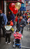 San Francisco, California, USA. Chinatown, Woman and Child Walking through Chinese New Year Street Market.