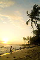 Children look for a last wave during sunset at  palm tree lined Hano beach in Kona on the Big Island of Hawaii.