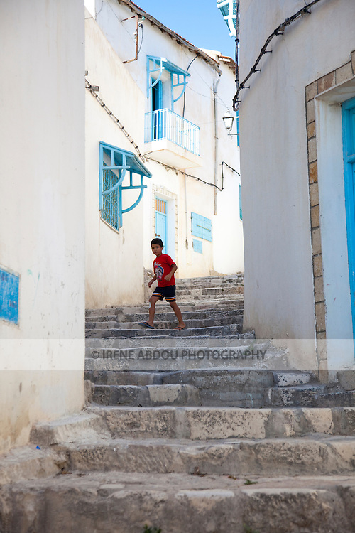 A boy runs down an alley in El Kef.  El Kef, the capital of Western Tunisia, is an interesting town speckled with winding alleys, whitewashed walls, and sea blue wooden doors decorated in traditional Tunisian fashion.