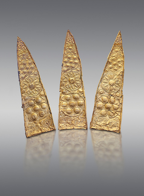 Top leaf shapes of a gold diadem from Grave III, 'Grave of a Women', Grave Circle A, Myenae, Greece. National Archaeological Museum Athens. Grey Background<br /> <br /> Shaft Grave III, the so-called 'Grave of the Women,' contained three female and two infant interments. The women were literally covered in gold jewelry and wore massive gold diadems, while the infants were overlaid with gold foil.