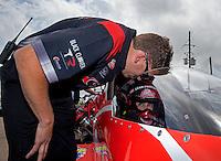 Apr 27, 2014; Baytown, TX, USA; NHRA top fuel dragster driver Leah Pritchett sits in her car as she talks to husband Gary Pritchett during the Spring Nationals at Royal Purple Raceway. Mandatory Credit: Mark J. Rebilas-
