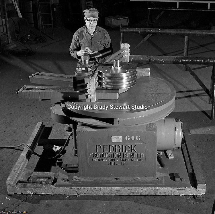 Client: The Pittsburgh Piping and Equipment Company<br /> Ad Agency: Pittsburgh Chamber of Commerce<br /> Contact: Mr. Emmerson<br /> Product: Fabricated Steel Pipe<br /> Location: Lawrenceville <br /> <br /> View of operator bending pipe with the new Pedrick Production Bender machine.  The manufacturer is the Pedrick Tool & Machine Company of Philadelphia Pennsylvania.  Photos were taken for the Pittsburgh Chamber of Commerce Display.<br /> <br /> Pittsburgh Piping and Equipment company started in 1928 and was a very successful fabricator and distributor of piping nationwide.