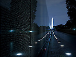 The wall of the Vietnam Veterans Memorial disappears into the distance as it leads towards the Washington Monument in the background.  Designed by Maya Ying Lin, 58,261 names are inscribed on the memorial, including some 1200 missing persons (missing in action, prisoners of war).