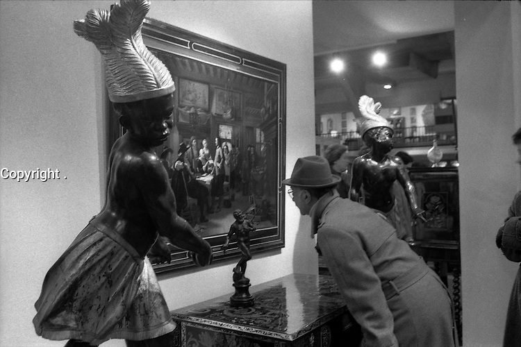 Parc des expositions. Le 6 Novembre 1980. Vue d'ensemble d' un stand au salon des antiquaires. Sur la droite un homme de profil se penche sur un tableau, pour voir les détails de l'oeuvre qui est entourée de deux sculptures d'enfants d'afrique noire.