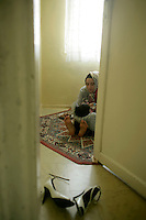 Girl rocking a baby to sleep in an apartment in Istanbul, Turkey
