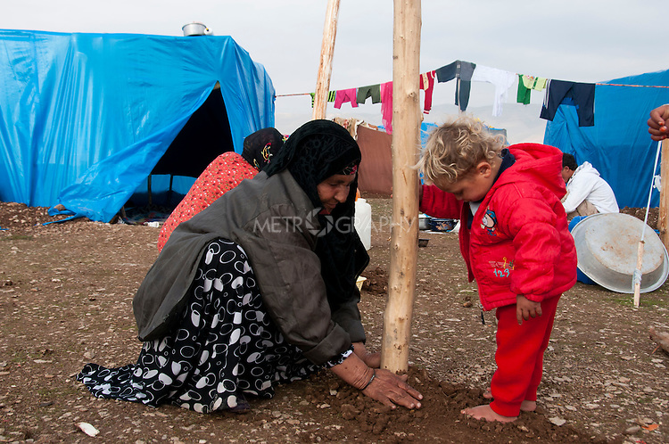 ARBAT, IRAQ: A Syrian woman packs dirt around a post for a shelter in the Arbat refugee camp...45 families who have fled the violence in Syria are currently living in the Arbat refugee camp 19km outside the Iraqi city of Sulaimaniyah...Photo by Zmnako Ismael/Metrography