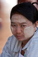 Myanmar, Burma.  Burmese Woman Wears Thanaka Paste on her Face as a Cosmetic Sunscreen.  Nyaung Oo, near Bagan.