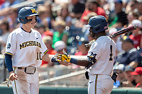 Michigan Wolverines third baseman Blake Nelson (10) is greeted by teammate Aka Thomas (4) during Game 11 of the NCAA College World Series against the Texas Tech Red Raiders on June 21, 2019 at TD Ameritrade Park in Omaha, Nebraska. Michigan defeated Texas Tech 15-3 and is headed to the CWS Finals. (Andrew Woolley/Four Seam Images)