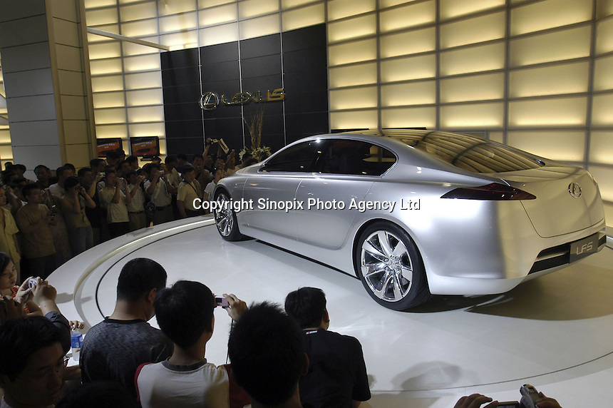 Visitors look at a Lexus LFS concept car at the Auto China 2004 exhibition in Beijing, China..
