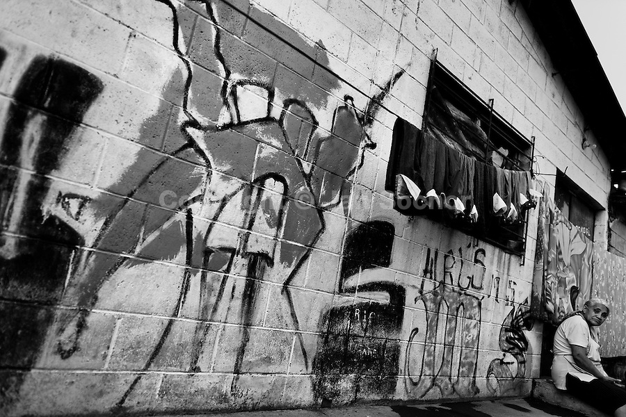 """A gang graffiti (""""Devil's horns"""") painted on the wall in the Mara Salvatrucha gang neighborhood in San Salvador, El Salvador, 19 May 2011. During the last two decades, Central America has become the deadliest region in the world that is not at war. According to the UN statistics, more people per capita were killed in El Salvador than in Iraq, in recent years. Due to the criminal activities of Mara Salvatrucha (MS-13) and 18th Street Gang (M-18), the two major street gangs in El Salvador, the country has fallen into the spiral of fear, violence and death. Thousands of Mara gang members, both on the streets or in the overcrowded prisons, organize and run extortions, distribution of drugs and kidnappings. Tattooed armed young men, mainly from the poorest neighborhoods, fight unmerciful turf battles with their coevals from the rival gang, balancing between life and death every day. Twenty years after the devastating civil war, a social war has paralyzed the nation of El Salvador."""