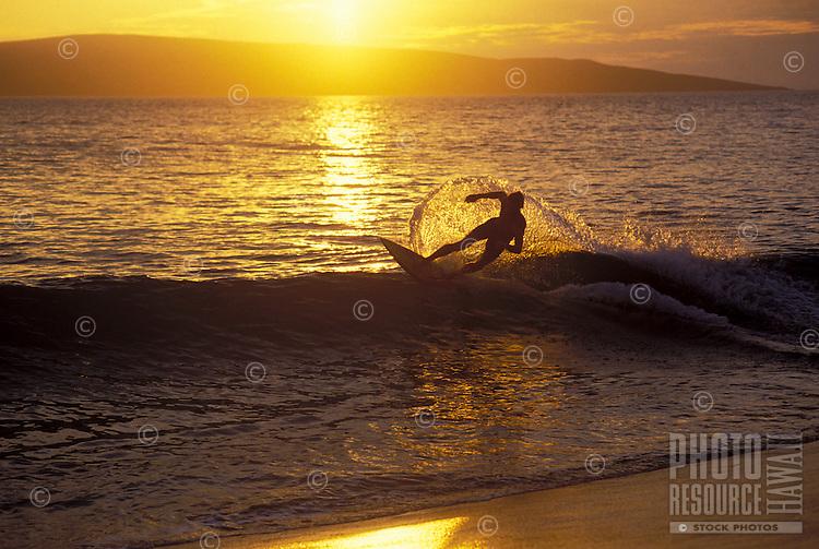 A skim boarder is backlit by a setting sun over Kahoolawe at Big Beach, Makena, Maui.