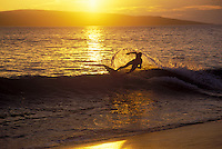 A skim boarder is backlit by a setting sun over Kahoolawe at Big Beach, Makena, Maui.