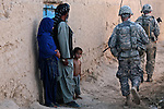 Villagers watch U.S. soldiers with Company A, 2nd Battalion, 2nd Infantry Regiment, pass by during a patrol in the village of Mir Hotak in Kandahar province, Afghanistan. April 15, 2009. DREW BROWN/STARS AND STRIPES