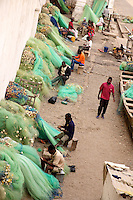 Fishermen mending nets beside Cape Coast Castle. The old fort was once part of the slave trade, and later became the center of British rule in what was called Gold Coast. .Photograph by Peter E. Randall