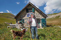 Bernard Bruno, sheep raiser, 47 years old, poses for the photographer with one of his sheepdogs in front of the shepherd's cabin where he lives alone during 3 summer months while his sheep graze the mountain pastures around the Plateau de Longon, Mercantour National Park, French Alps, France, 01 August 2013.