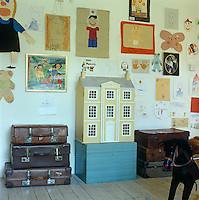 A doll's house flanked by tiers of battered leather suitcases against a wall of the nursery which is covered with children's paintings, drawings and cut-outs