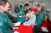 Paramedic ambulance crew have brought a child with a broken arm into the A&E department of a hospital. The child has been transported to hospital in an ambulance wearing a removable splint. This image may only be used to portray the subject in a positive manner..©shoutpictures.com..john@shoutpictures.com