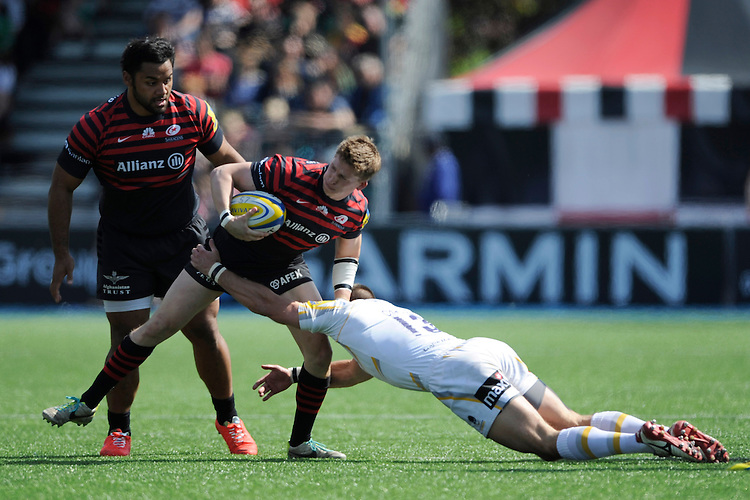 David Strettle of Saracens is tackled by Alex Grove of Worcester Warriors during the Aviva Premiership match between Saracens and Worcester Warriors at Allianz Park on Saturday 3rd May 2014 (Photo by Rob Munro)