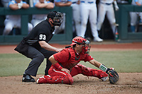 North Carolina State Wolfpack catcher Luca Tresh (24) reaches for a pitch in the dirt as home plate umpire Adam Dowdy looks on during the game against the North Carolina Tar Heels at Boshamer Stadium on March 27, 2021 in Chapel Hill, North Carolina. (Brian Westerholt/Four Seam Images)
