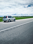 Moving single car on Trans-Canada highway traveling through Manitoba, outdoor scenery. Manitoba, Canada.