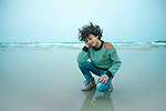 A boy with afro hairstyle have fun on the beach. Photo by Sanad Ltefa