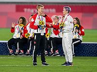 YOKOHAMA, JAPAN - AUGUST 6: Quinn #5 of Canada talks with Megan Rapinoe #15 of the USWNT at International Stadium Yokohama on August 6, 2021 in Yokohama, Japan.