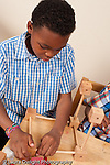 8 year old boy playing with wood and stick construction toy vertical